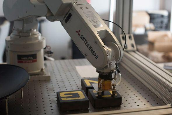 mitsubishi robotic arm moving Cognex logo blocks